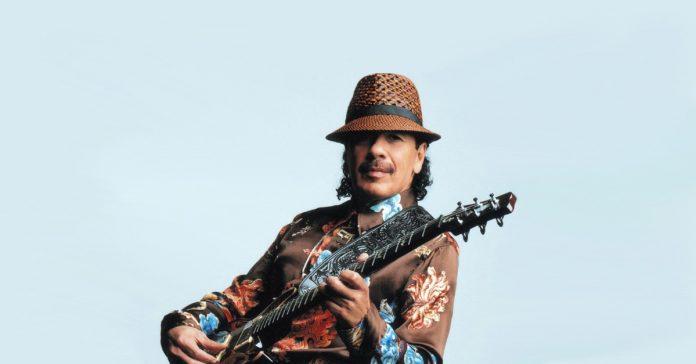 Santana posando para foto com uma guitarra PRS