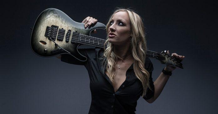 Nita Strauss segurando uma guitarra Ibanez sobre os ombros