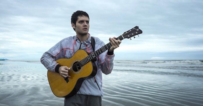 Daniel Padim tocando violão na praia
