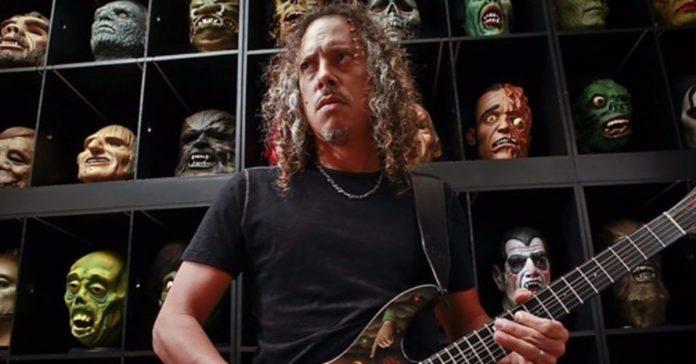 Kirk Hammett tocando guitarra com bonecos de terror ao fundo