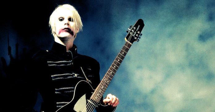 John 5 posando para foto com uma guitarra preta